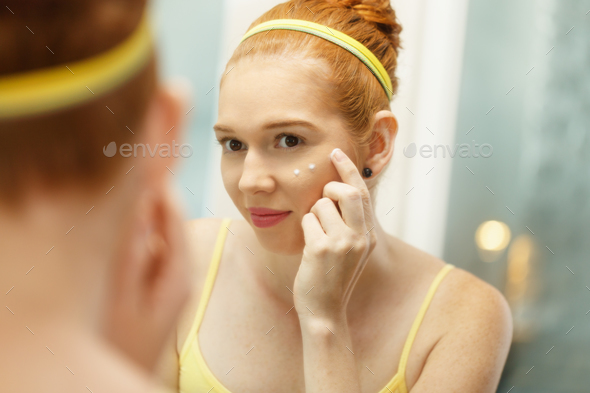 Young Woman Applies Anti-Aging Cream Looking At Mirror - Stock Photo - Images