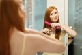 Beautiful Woman Ironing Healthy Red Hair With Iron Straightener - PhotoDune Item for Sale