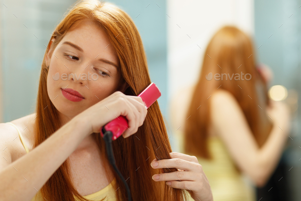 Beautiful Woman Ironing Healthy Red Hair With Iron Straightener - Stock Photo - Images