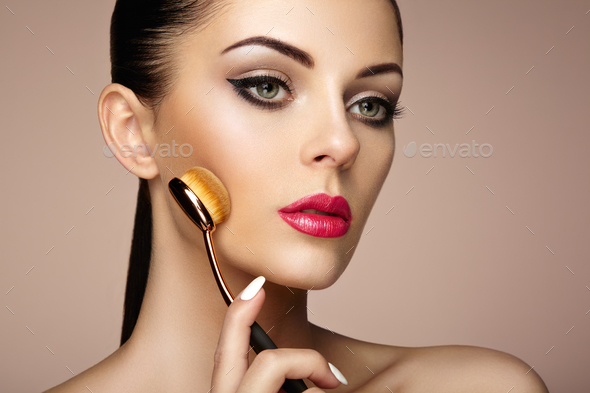 Makeup artist applies skintone with brush - Stock Photo - Images