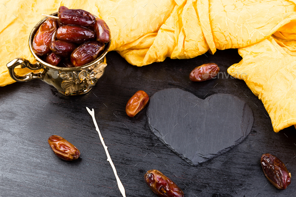 Dry fruit dates in golden cup near slate black heart. Copy space.Valentine Day. - Stock Photo - Images