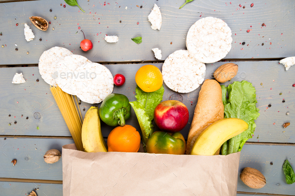 Grocery shopping concept. Different food in paper bag on wooden background.  Flat lay. - Stock Photo - Images