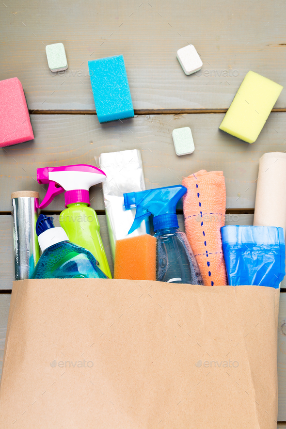 Full paper bag of different house cleaning product on wooden table. - Stock Photo - Images