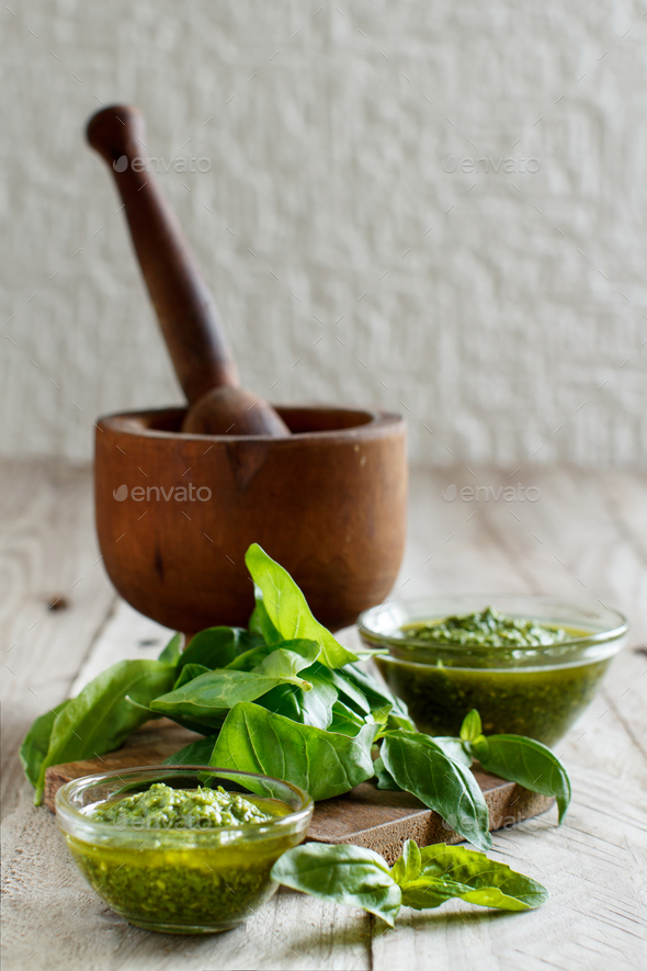Pesto sauce and fresh basil on a wooden table - Stock Photo - Images