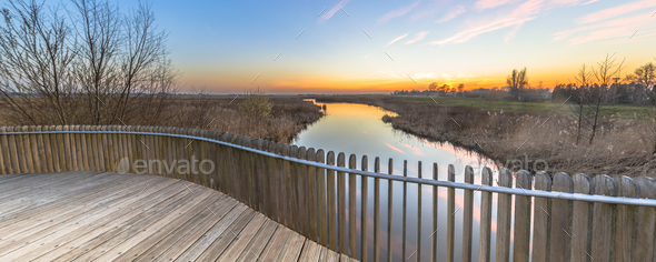Wooden balustrade sunset over swamp - Stock Photo - Images