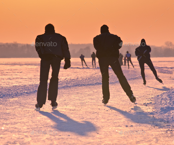 Ice Skaters on frozen lake at  sunset - Stock Photo - Images