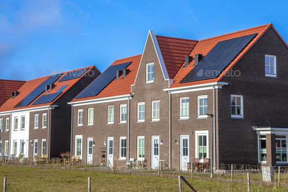Modern row houses with  solar panels on sunny day - Stock Photo - Images