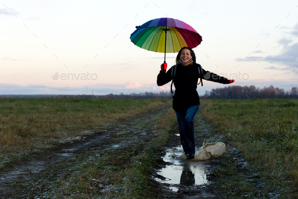 Young emotional woman with an umbrella on a walk, nature light - Stock Photo - Images