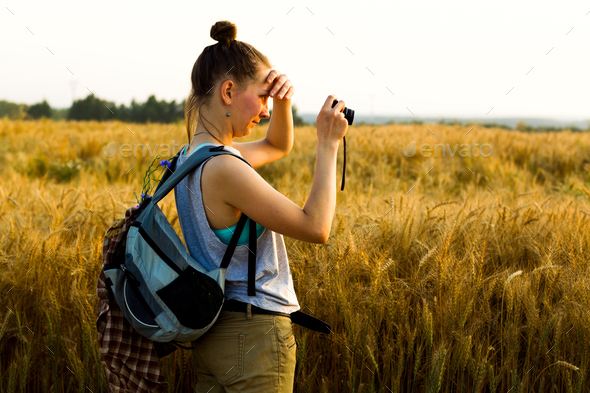Young girl takes pictures of the sunset on a summer evening - Stock Photo - Images