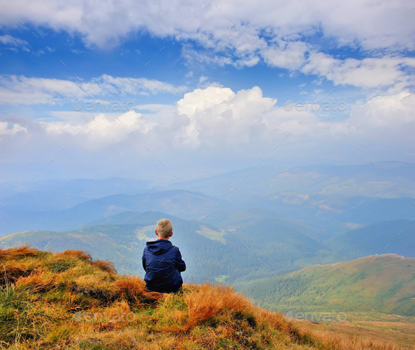 A tourist sits and looks into the distance. Man sit. Wonderful m - Stock Photo - Images