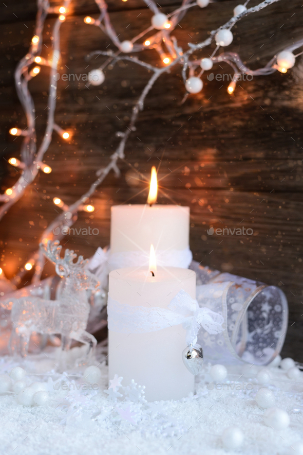 Two burning candles with a deer with christmas decorative balls - Stock Photo - Images