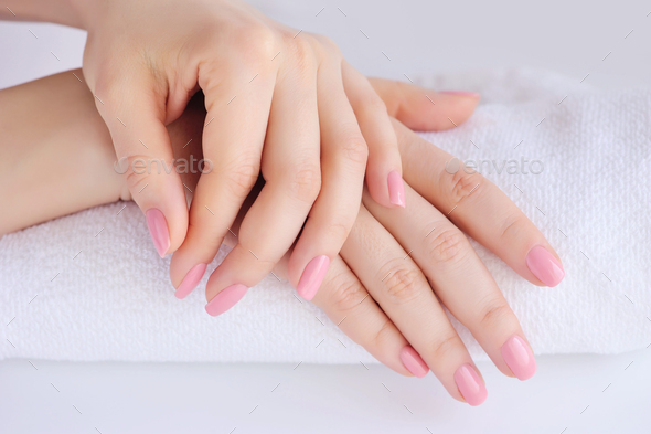 Hands of a woman with pink manicure are on a towel - Stock Photo - Images