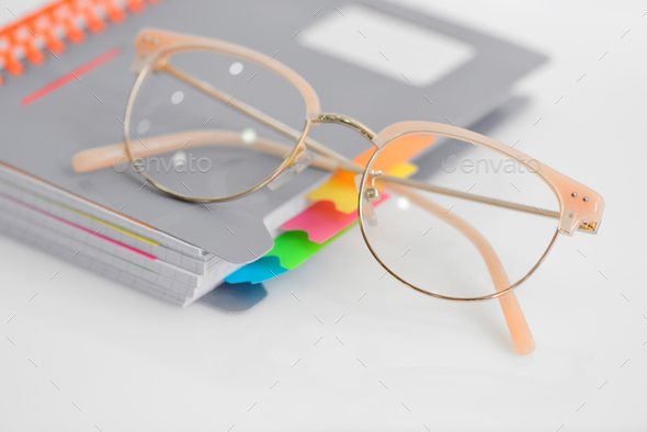 Eye glasses with spiral notebook on white background - Stock Photo - Images