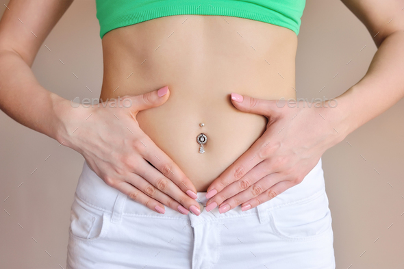 Woman holding hands on a belly. Stomach health concept - Stock Photo - Images