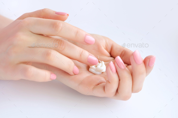 Young woman with pink manicure applies cream on her hands - Stock Photo - Images