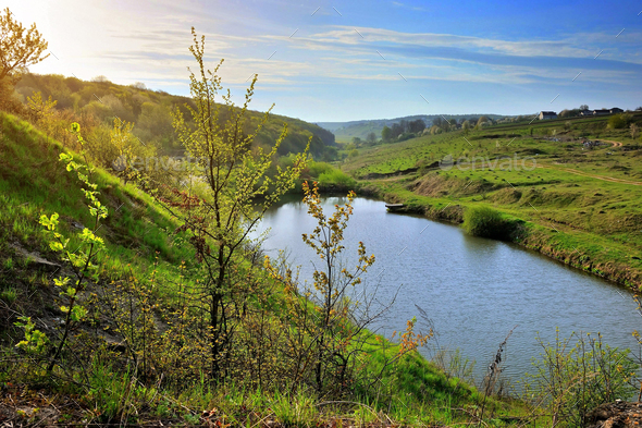 Spring sunny landscape with a lake. View from the hill - Stock Photo - Images