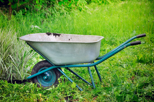 Old wheelbarrow on a green grass field background - Stock Photo - Images