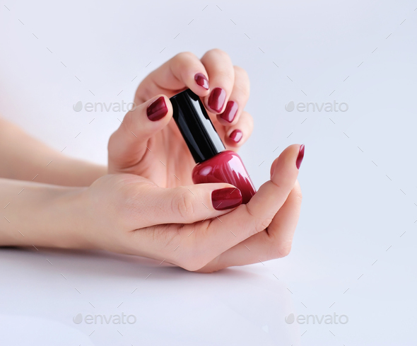 Hands of a woman with dark red manicure and nail polish bottle - Stock Photo - Images