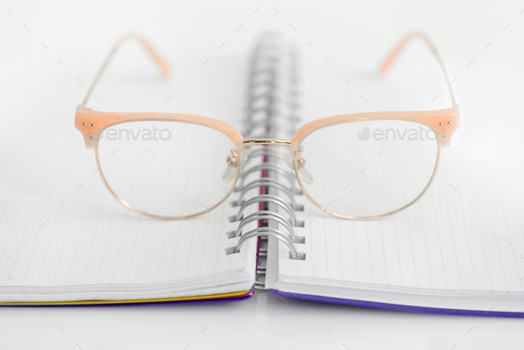 Eye glasses with opened blank spiral notebook on white backgroun - Stock Photo - Images