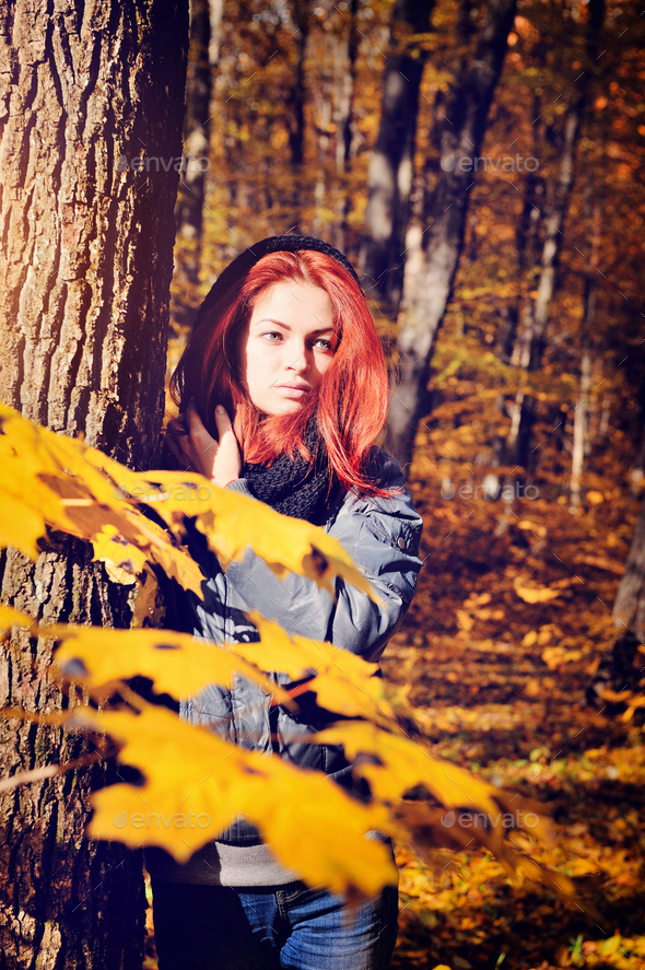 Red-haired girl walking in the autumn forest - Stock Photo - Images