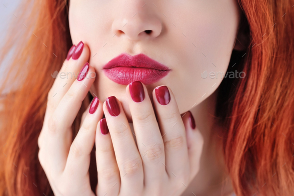 Beautiful red-haired young woman with dark red manicure, lipstic - Stock Photo - Images
