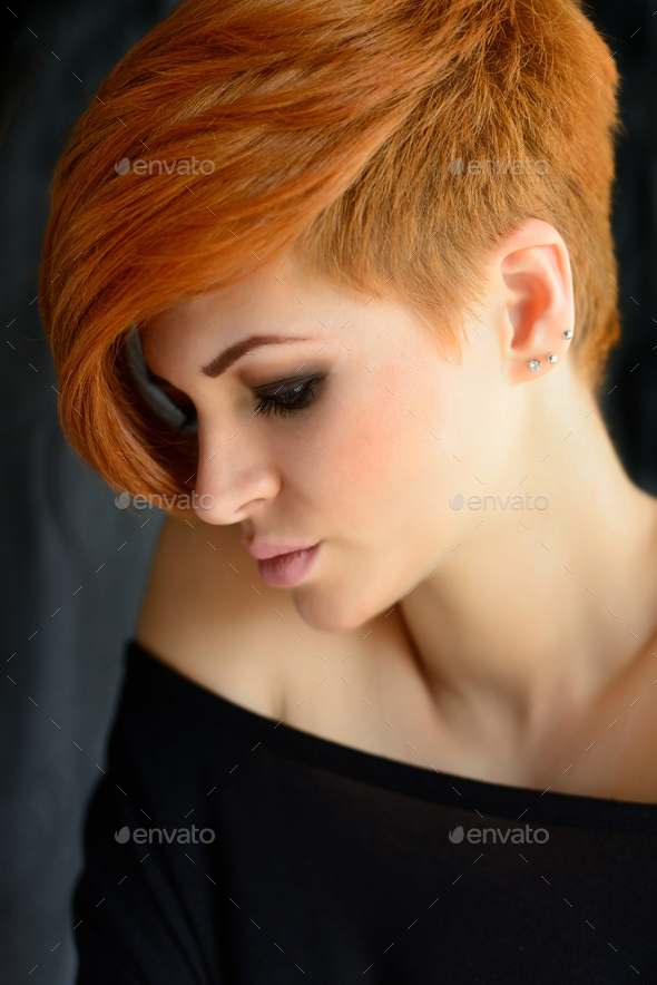 Portrait of a beautiful young red-haired woman with short hair - Stock Photo - Images