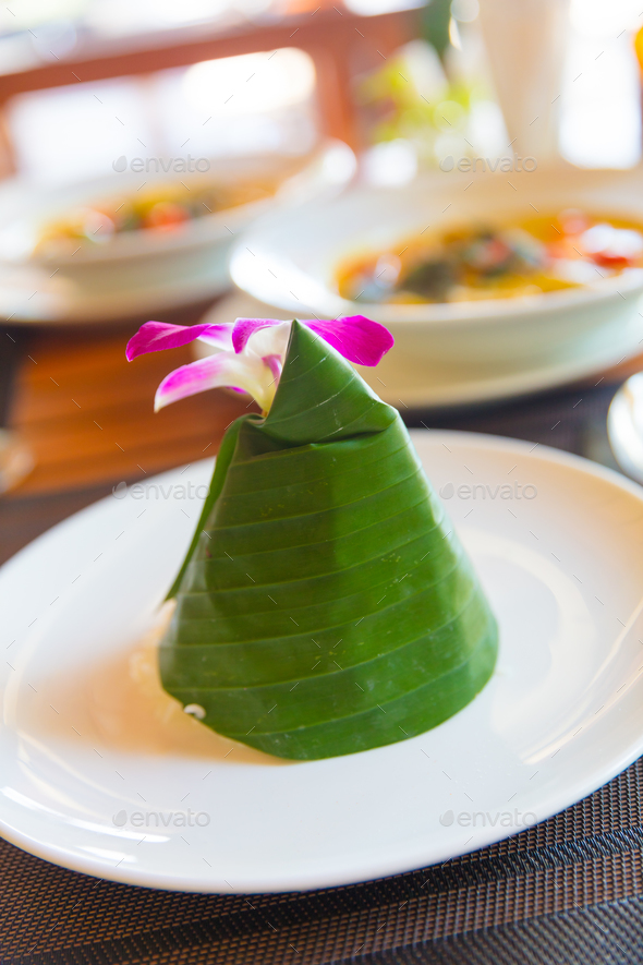 Steam Rice Wrapped In Cone Shape Banana Leaf With Orchid - Stock Photo - Images