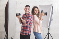 two young photographers back to back smiling while looking at ca - PhotoDune Item for Sale