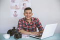 young photographer sitting on his office while working on laptop - PhotoDune Item for Sale