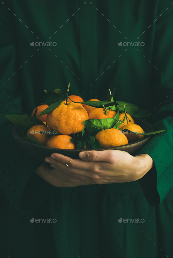 Fresh tangerine fruit with leaves in plate in female hands - Stock Photo - Images