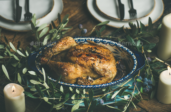 Whole roasted chicken with garlic decorated with olive tree branch - Stock Photo - Images