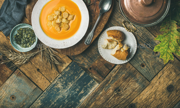 Fall pumpkin cream soup with croutons and seeds, flat-lay - Stock Photo - Images