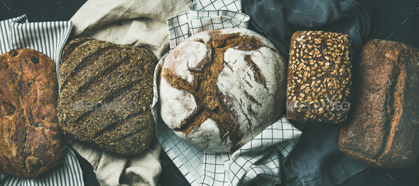 Flat-lay of Various bread selection loaves, black background - Stock Photo - Images