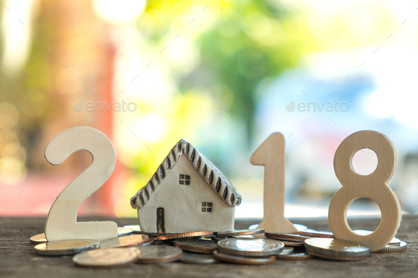 Number two, one, eight, put on coins,Model house replaced by zero.All laid on wooden floor. - Stock Photo - Images