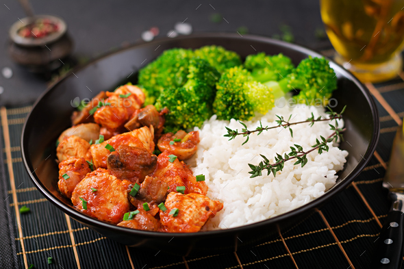 Pieces of chicken fillet with mushrooms stewed in tomato sauce with boiled broccoli  - Stock Photo - Images