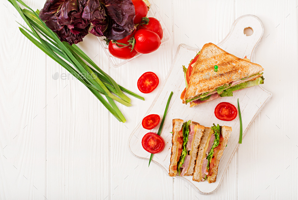 Club sandwich - panini with ham, cheese, tomato and herbs. Top view - Stock Photo - Images