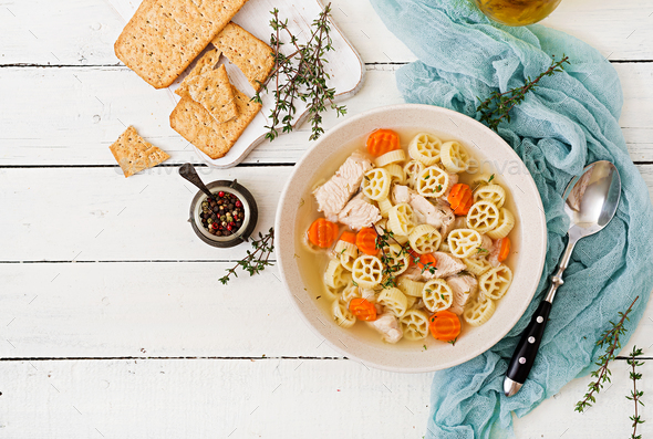 Dietary soup with turkey or chicken fillet with pasta Ruote and herbs. Flat lay. Top view - Stock Photo - Images