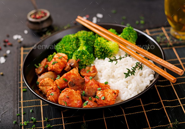 Pieces of chicken fillet with mushrooms stewed in tomato sauce with boiled broccoli and rice. - Stock Photo - Images