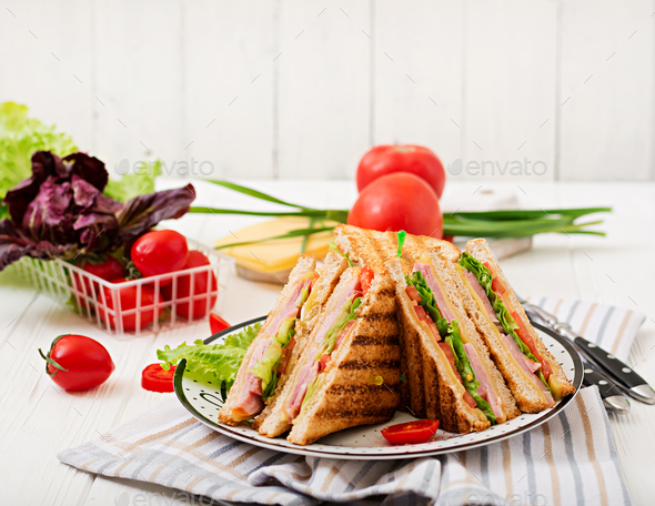 Club sandwich - panini with ham, cheese, tomato and herbs. - Stock Photo - Images
