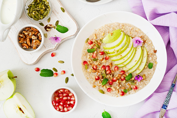 Tasty and healthy oatmeal porridge with apples, pomegranate and nuts. - Stock Photo - Images