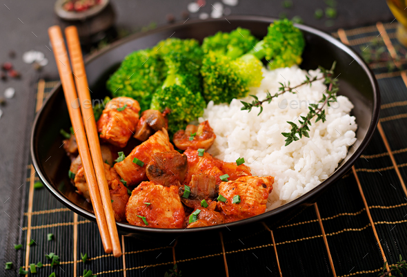Pieces of chicken fillet with mushrooms stewed in tomato sauce with boiled broccoli and rice - Stock Photo - Images
