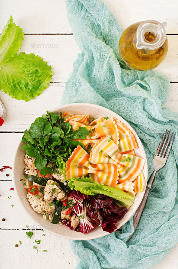 Farfalle pasta durum wheat with baked chicken fillet with eggplant, zucchini and salad in bowl. - Stock Photo - Images