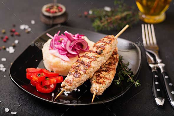 Minced Lula kebab grilled turkey (chicken) with fresh tomato and bulgur - Stock Photo - Images