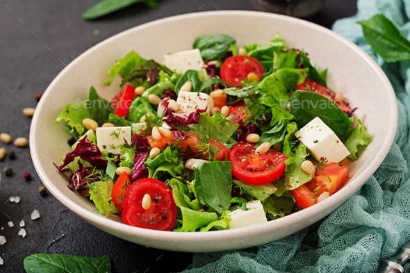 Dietary salad with tomatoes, feta, lettuce, spinach and pine nuts. - Stock Photo - Images