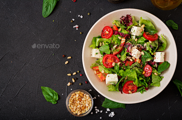 Dietary salad with tomatoes, feta, lettuce, spinach and pine nuts. Top view. Flat lay. - Stock Photo - Images