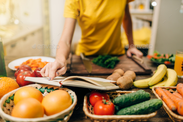 Young woman cooking on recipes, healthy bio food - Stock Photo - Images