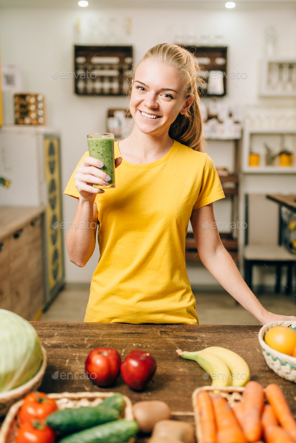 Woman with cocktail of fresh fruit and vegetables - Stock Photo - Images