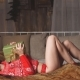 Free Download Young Sexy girl in Red sweater lying on bed with Christmas gift in hands Nulled