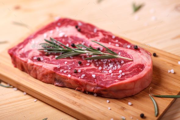 raw uncooked marble beef steak ribeye with rosemary - Stock Photo - Images