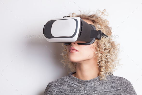 young curly blonde woman in VR glasses - Stock Photo - Images